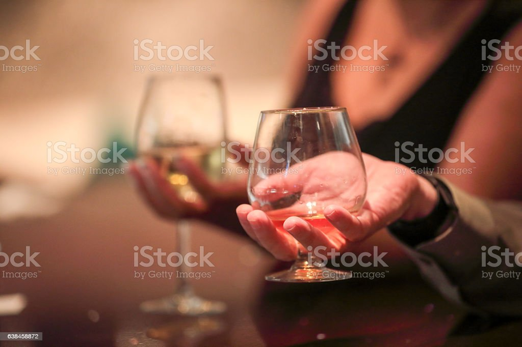 Male hand holding brandy snifter and woman with wine glass stock photo