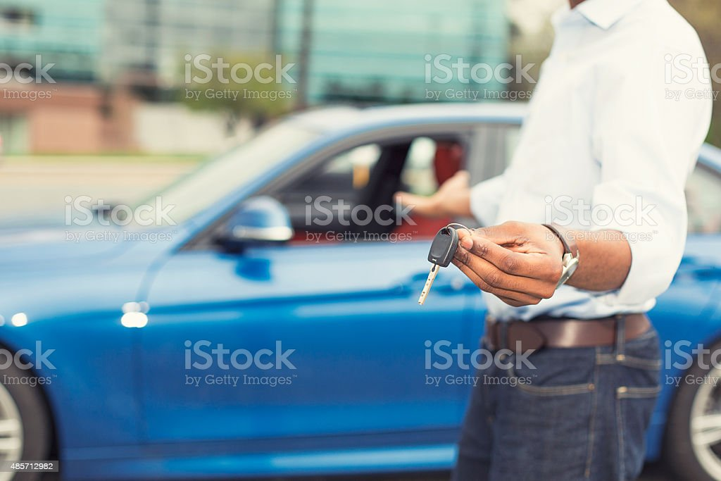 Male hand holding car keys offering car on background stock photo