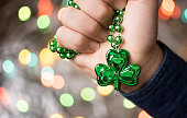 Male hand holding clover green necklace