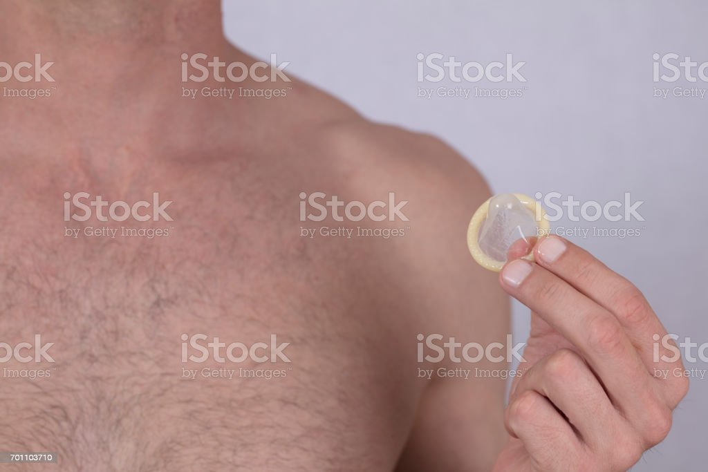 Male hand holding condom. Prevention of sexually transmitted diseases. Health care and STD prevention concept. stock photo