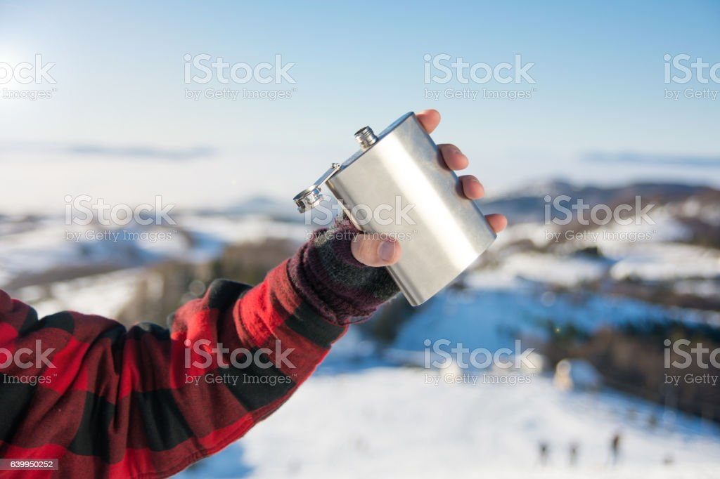 Male hand holding hip flask on a snowy mountain stock photo