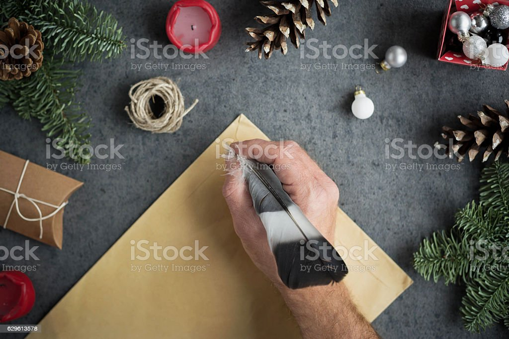 Male hand holding in hand ink pen and writing letter. stock photo