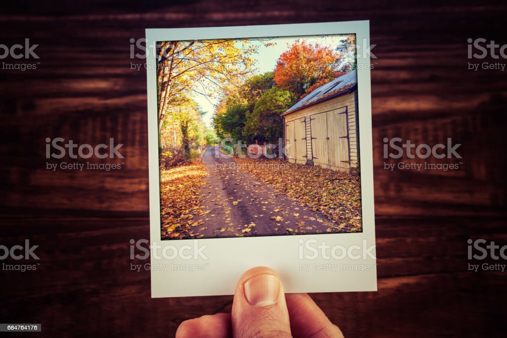 Male hand holding instant photo of rural road passing wooden shed among yellow and orange trees in Autumn Australia. Travel memories scrapbooking stock photo