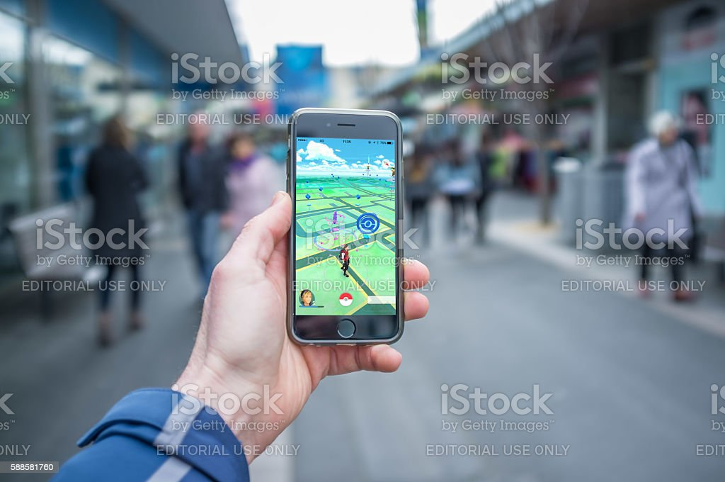 Male hand holding iPhone 6 with Pokemon Go stock photo
