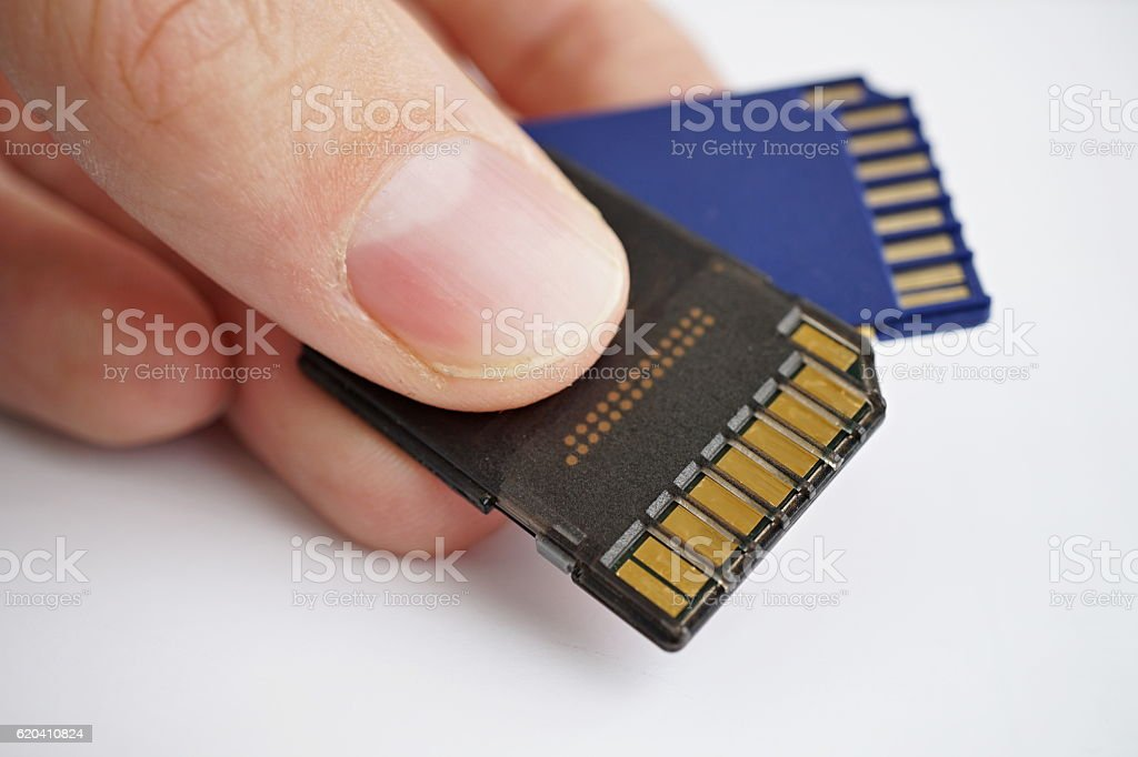 Male hand holding isolated plastic compact memory cards stock photo