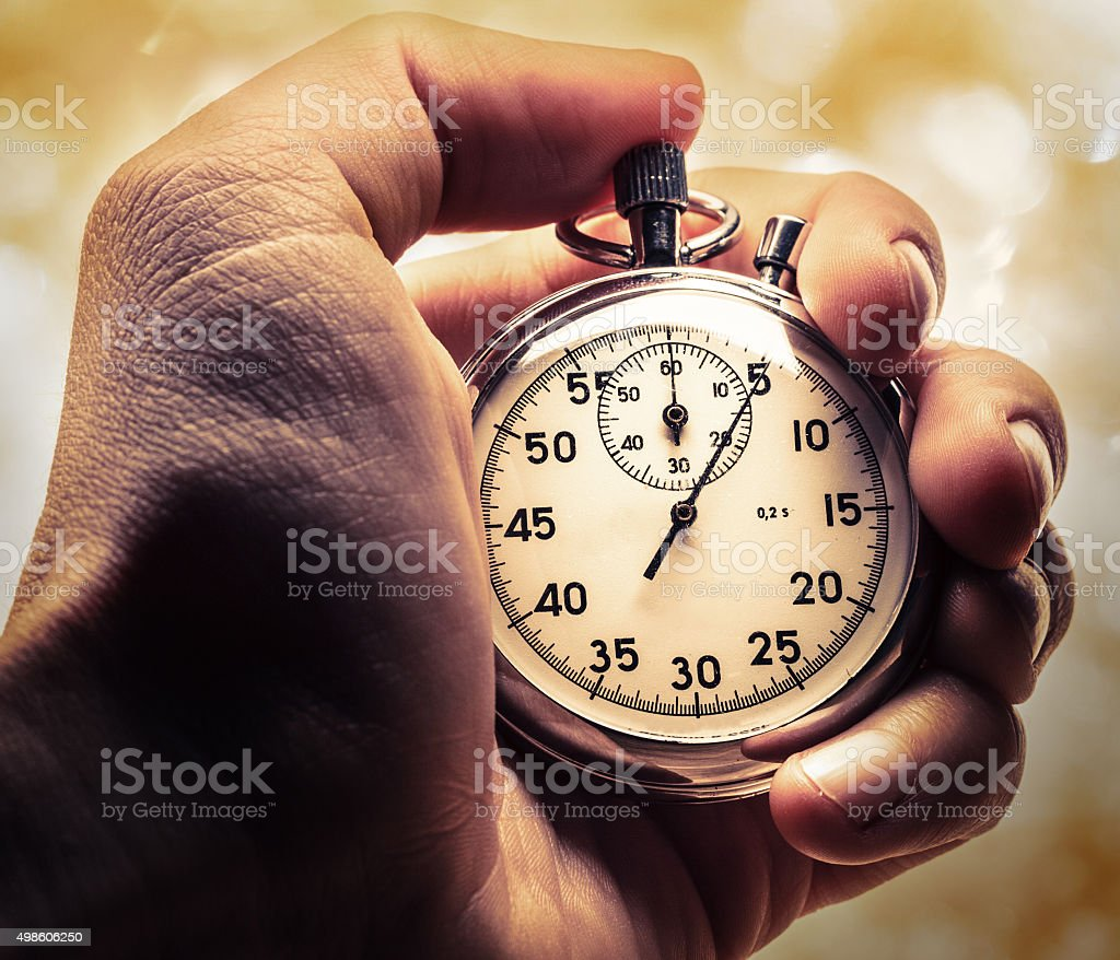 Male hand holding stopwatch stock photo