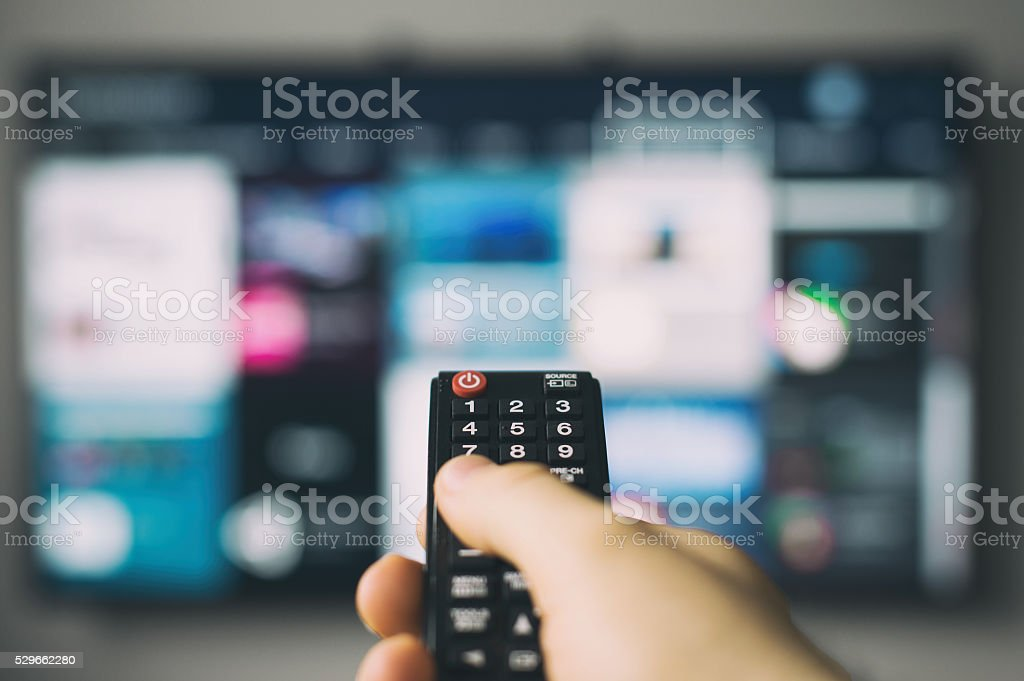 Male hand holding TV remote control. stock photo