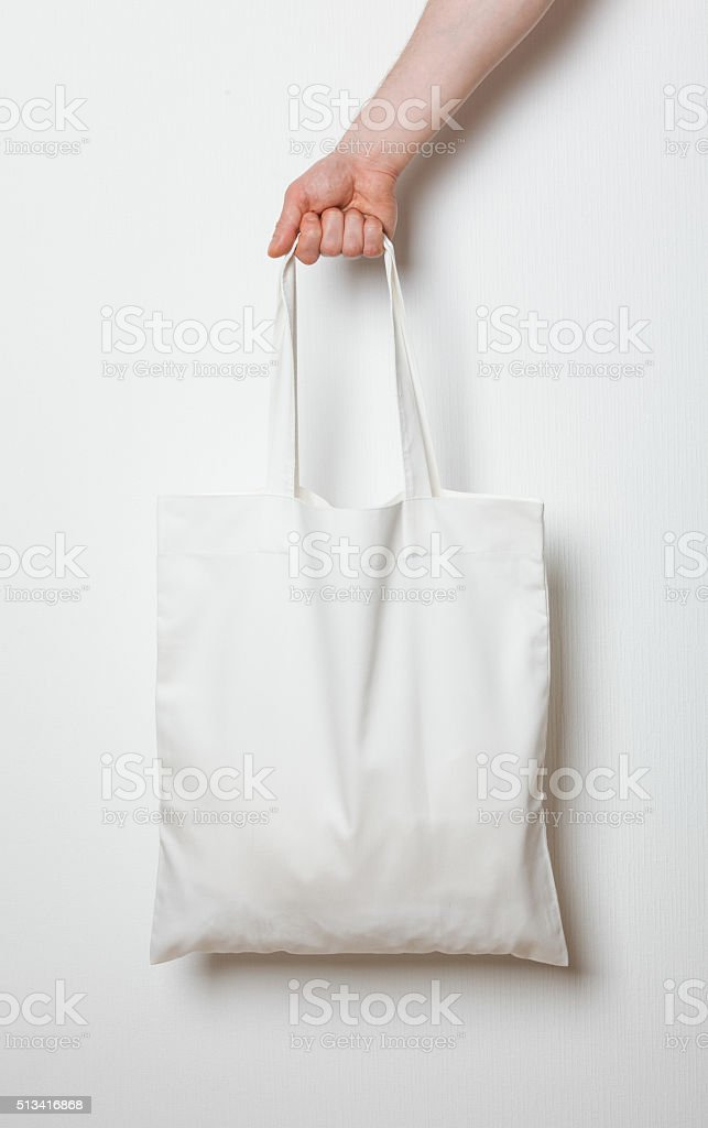 Male hand holding white textile bag stock photo