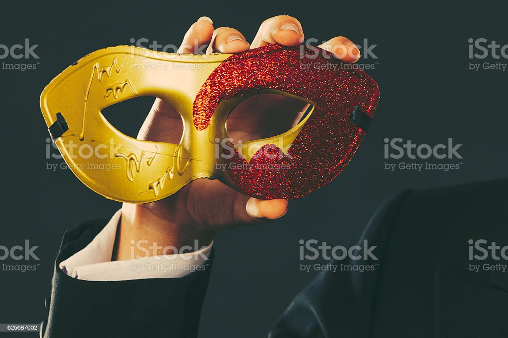Male hand holds carnival mask closeup stock photo