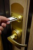 Male Hand Inserting Key Card Into Hotel Room Door Lock
