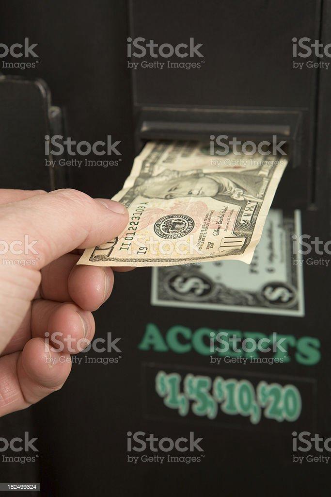 Male Hand Inserting Ten Dollar Bill into Change Machine royalty-free stock photo