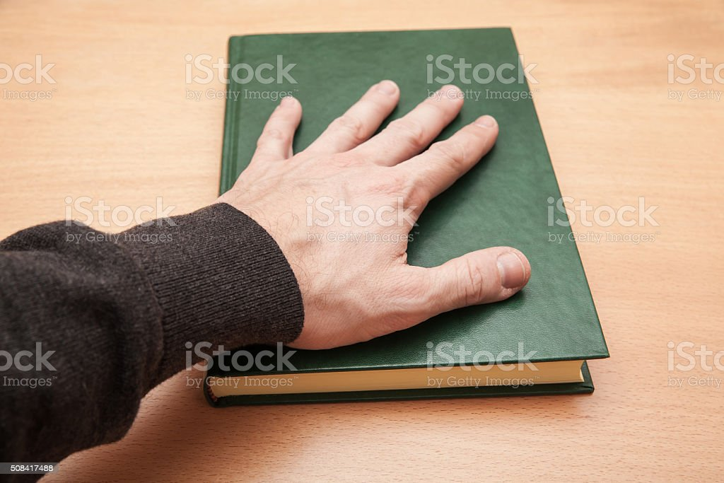 Male hand laying on book, swear concept stock photo