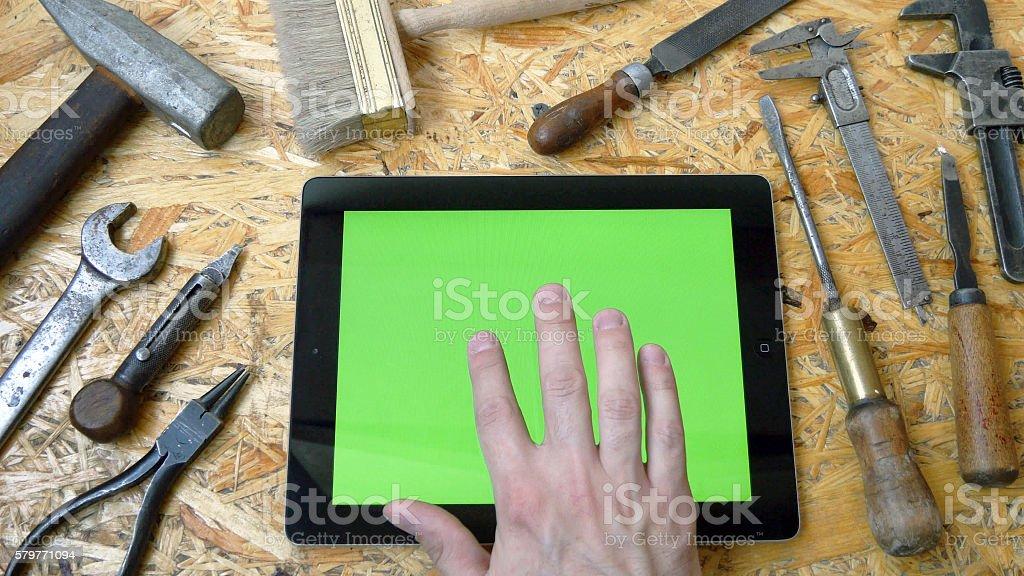 Male hand of artisan craftsman using tablet pc with green foto de stock libre de derechos