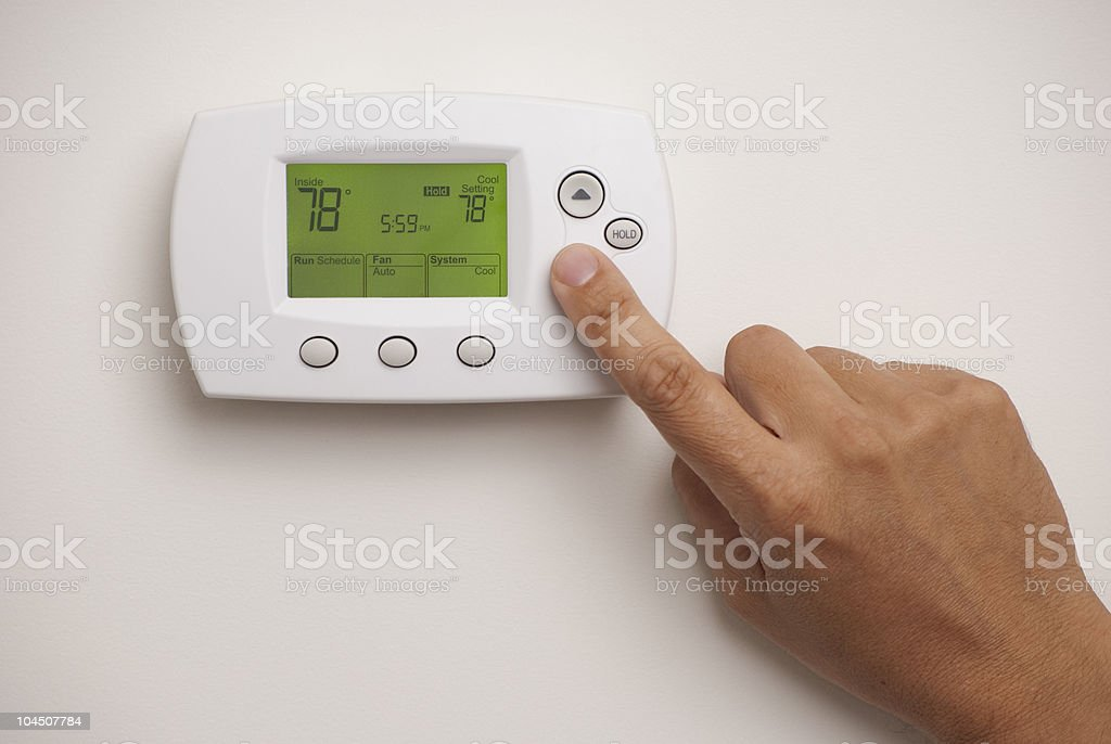 Male hand on digital thermostat set at 78 degrees stock photo