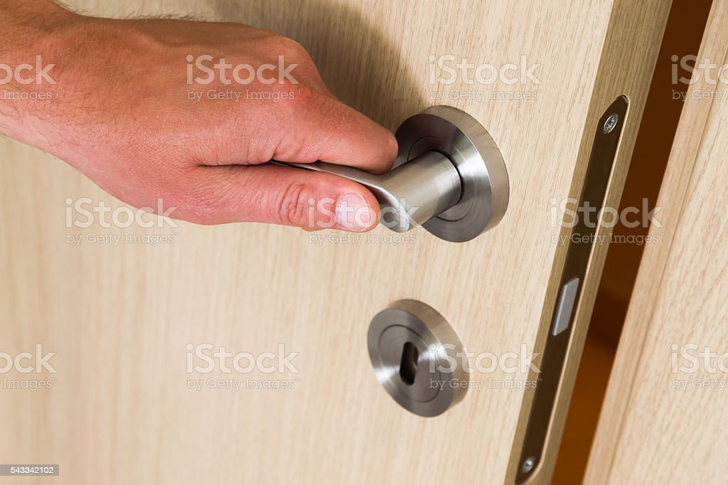 Male hand opening a wooden door stock photo