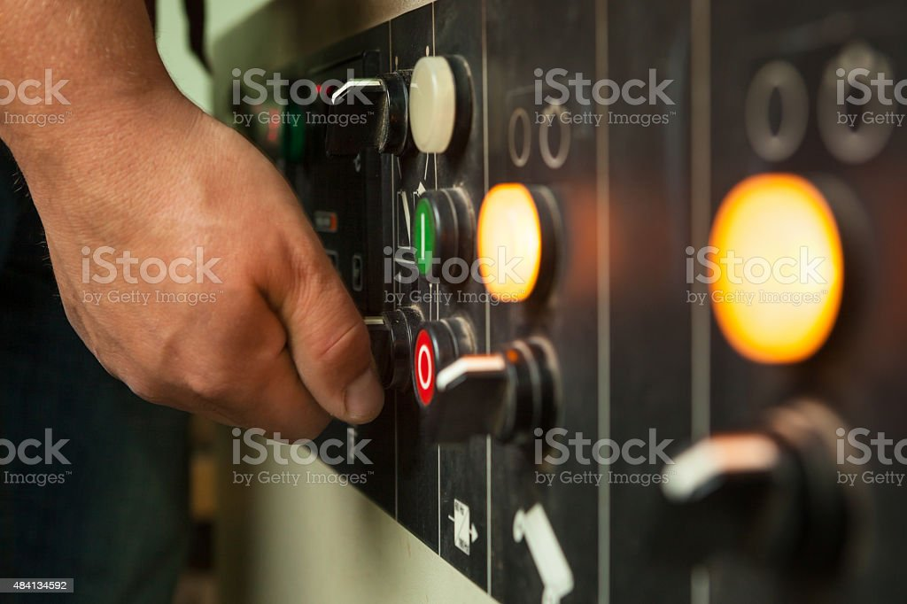 Male hand operating switches and buttons. stock photo