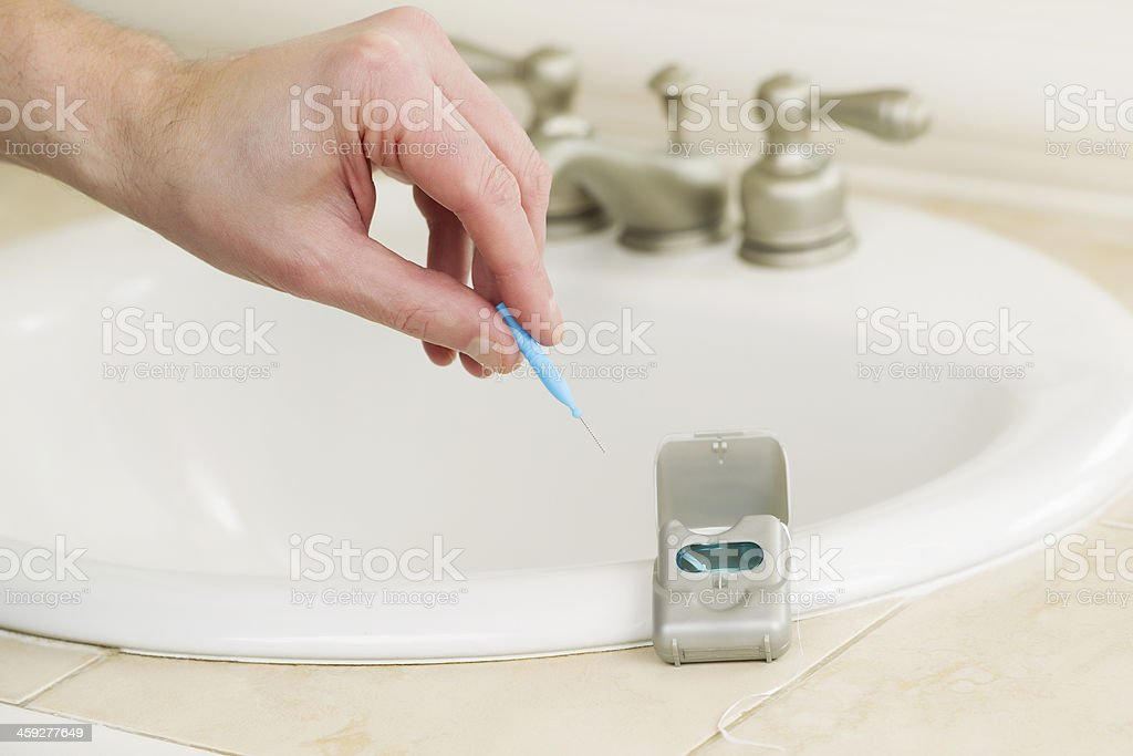 male hand picking up dental tooth pick stock photo