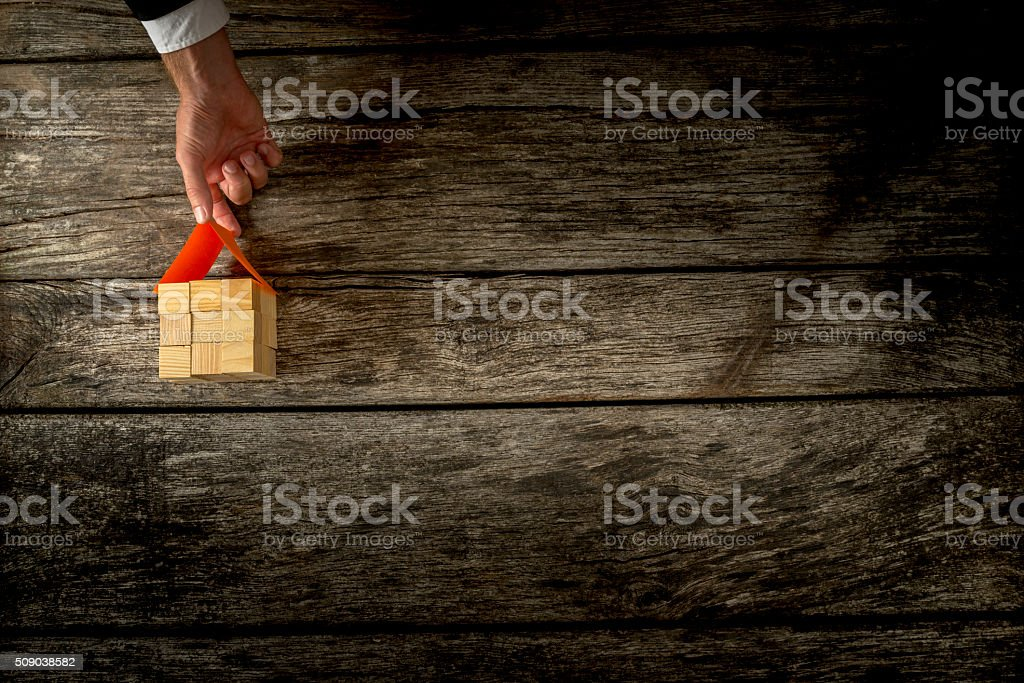 Male hand placing paper roof on top of a house stock photo