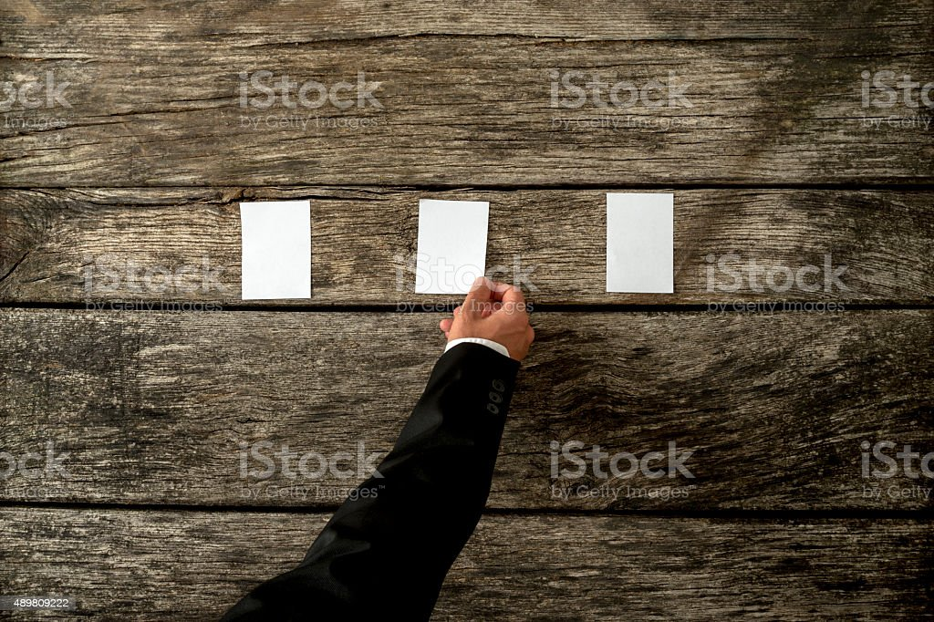 Male hand placing three blank white cards in a row stock photo