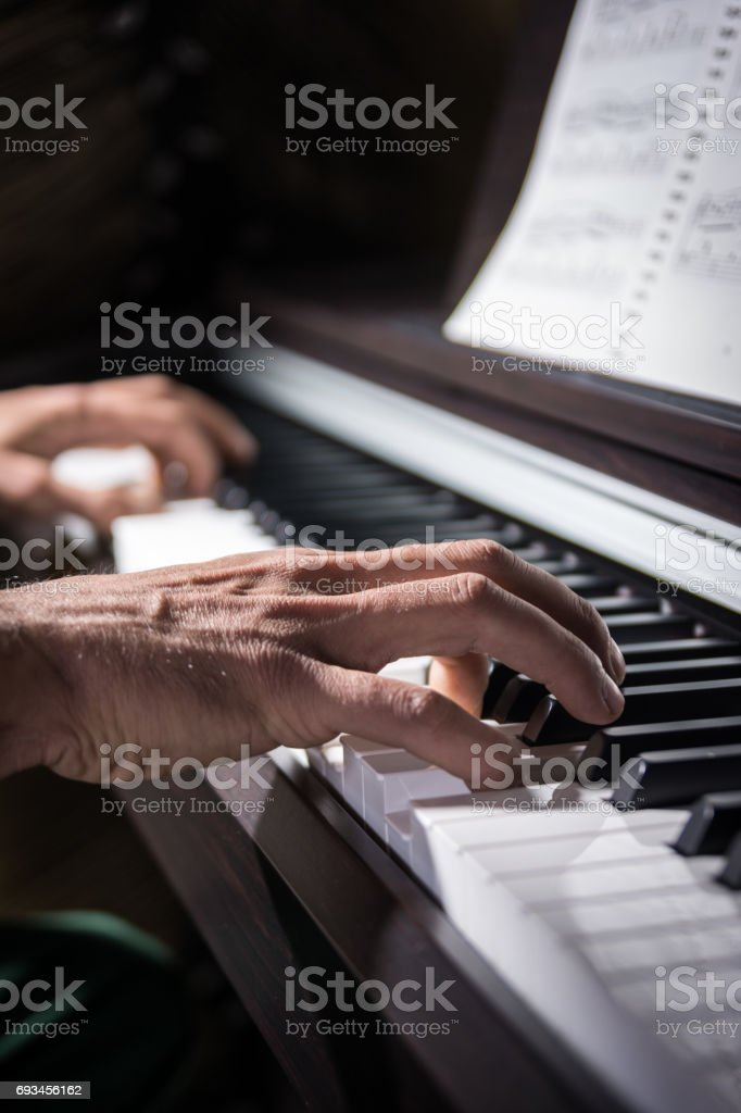 Male hand playing the keys of piano stock photo