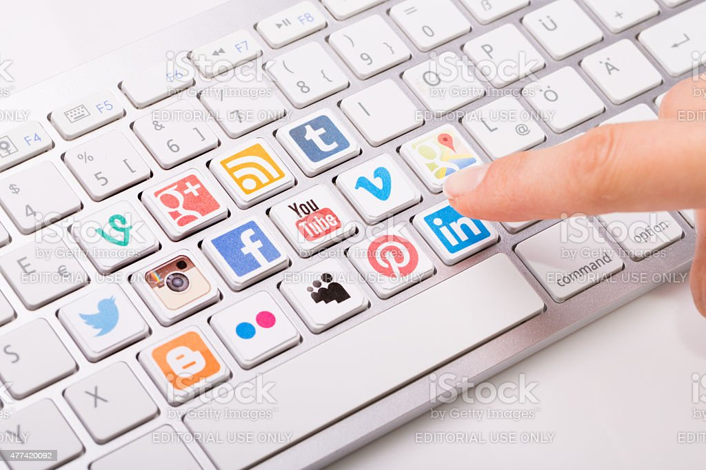 Male hand pointing a social media logotype collection printed an stock photo