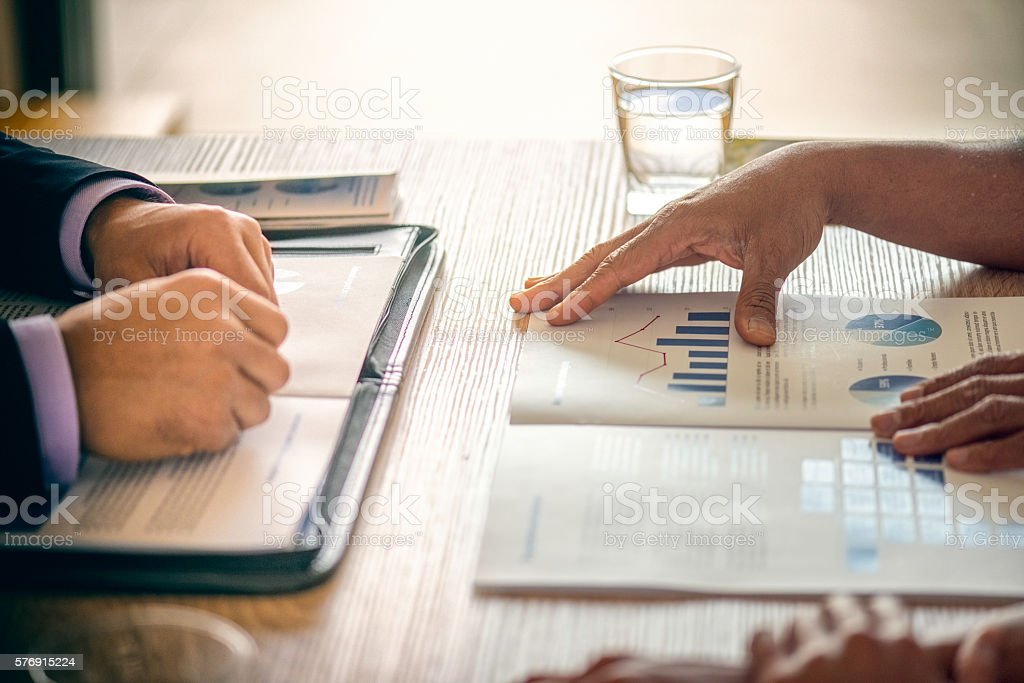 Male hand pointing at business document during discussion at meeting stock photo