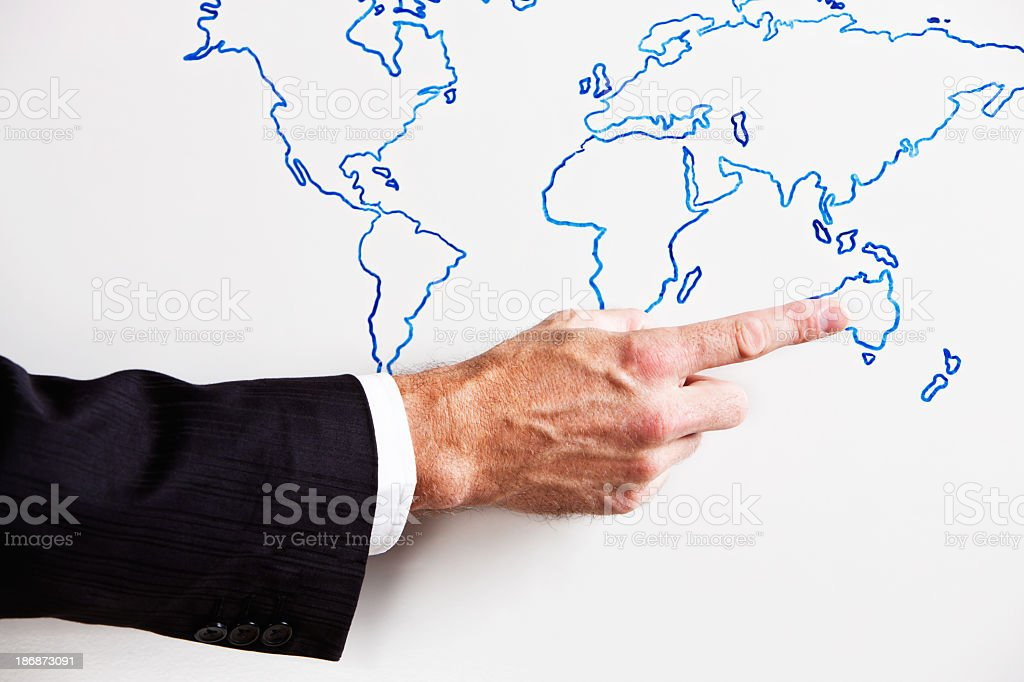 Male hand points to Australia on hand-drawn map royalty-free stock photo