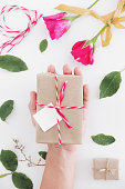 Male hand preparing gift for valentines day, on white table