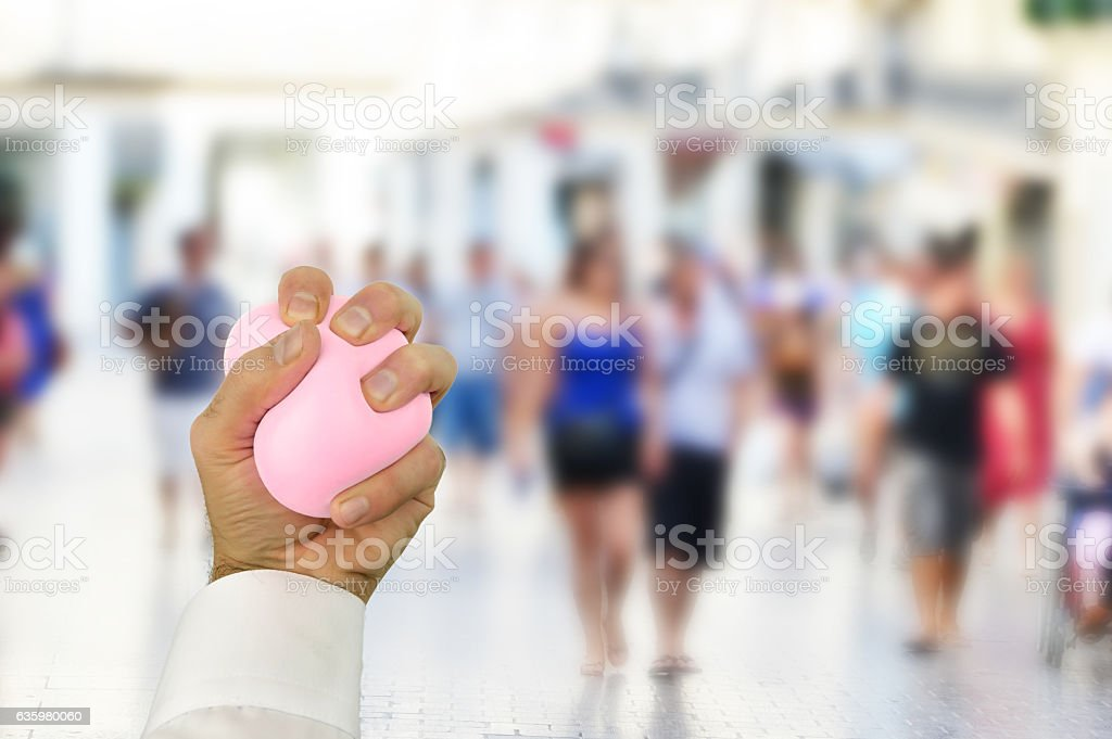 male hand pressing stress ball stock photo