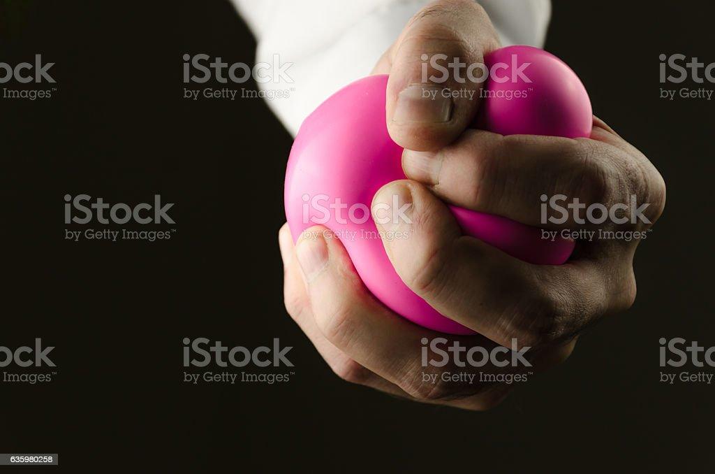 male hand pressing stress ball stock photo