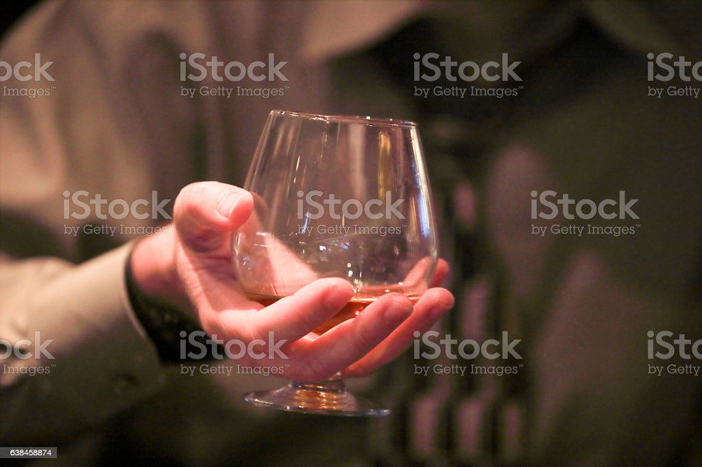 Male hand properly holding brandy snifter stock photo