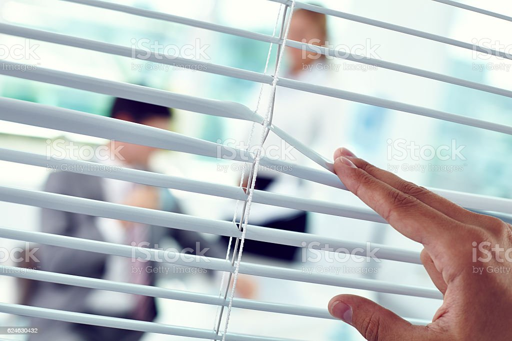 Male hand pulling office blinds apart to peek stock photo