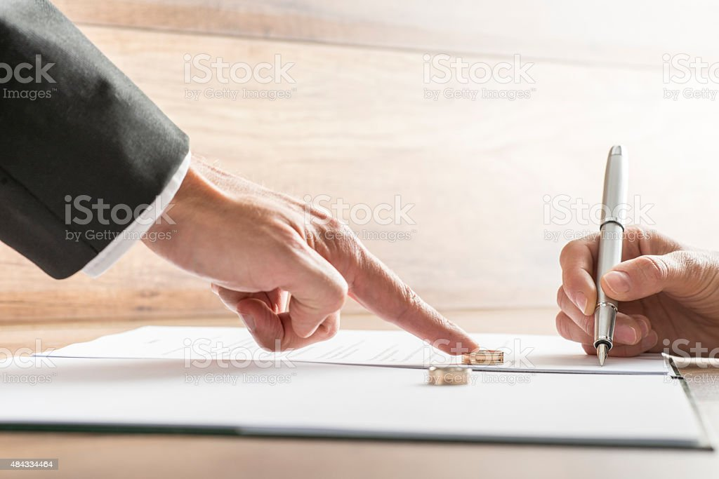 Male hand pushing a wedding ring over to  female hand stock photo