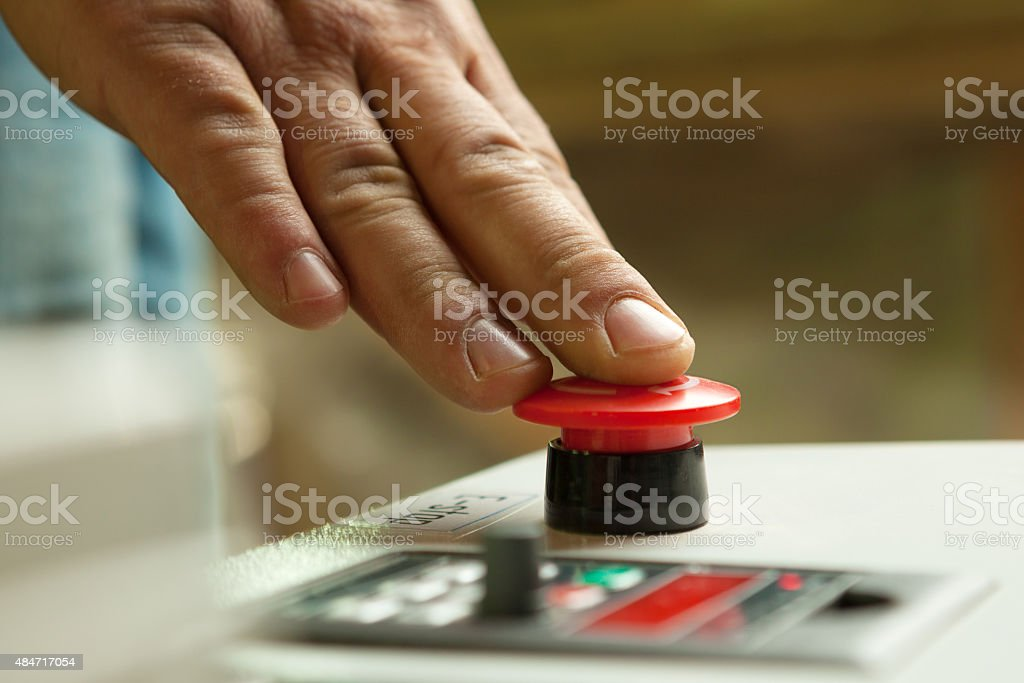 Male hand pushing emergency stop button. stock photo