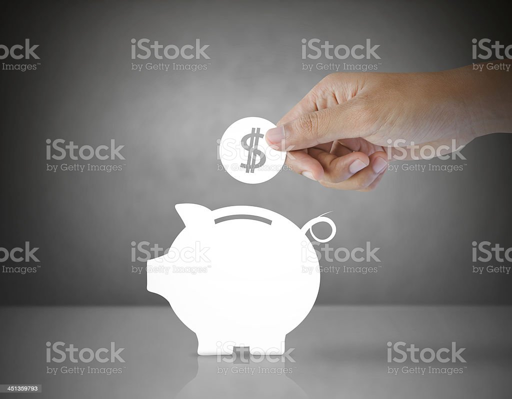 Male hand putting paper coin into a piggy bank stock photo