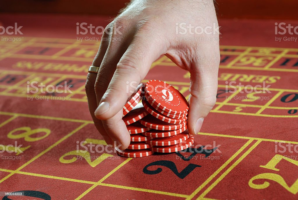 Male hand putting red poker chips into game stock photo