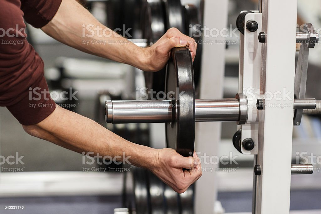 Male hand putting weight plate on barbell stock photo