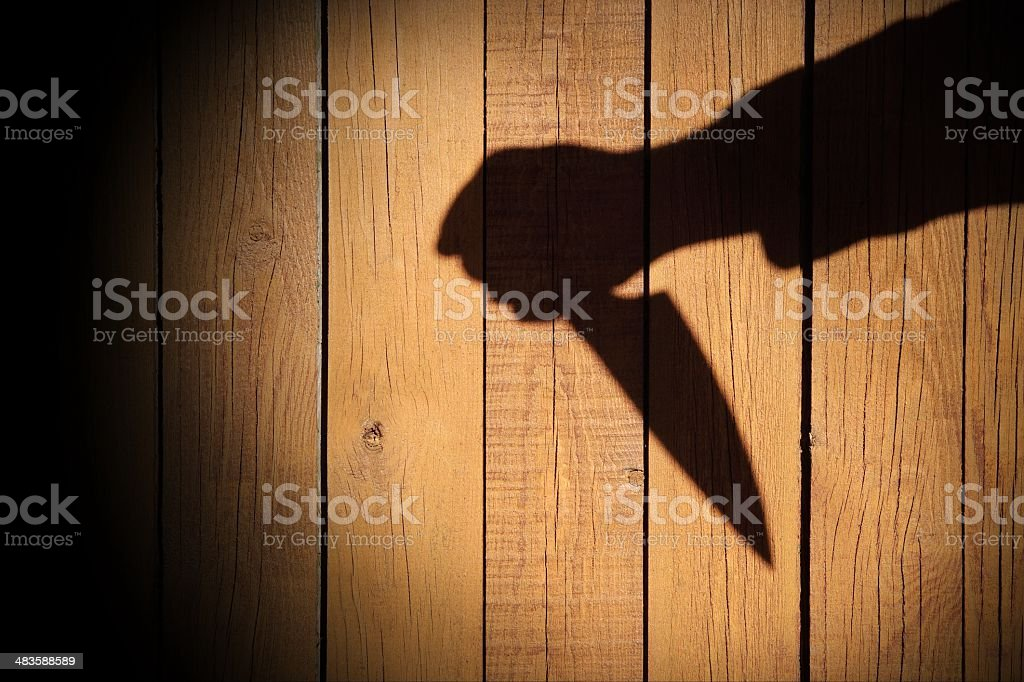 Male Hand Shadow with Kitchen Knife, on wooden background, XXXL stock photo