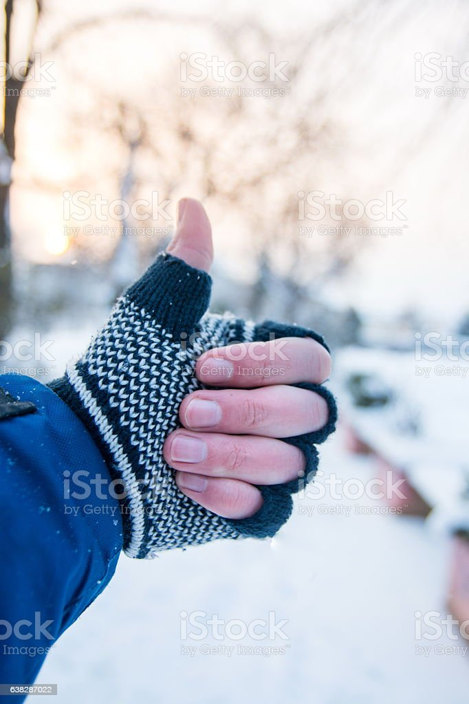 Male hand showing thumbs up in winter gloves stock photo