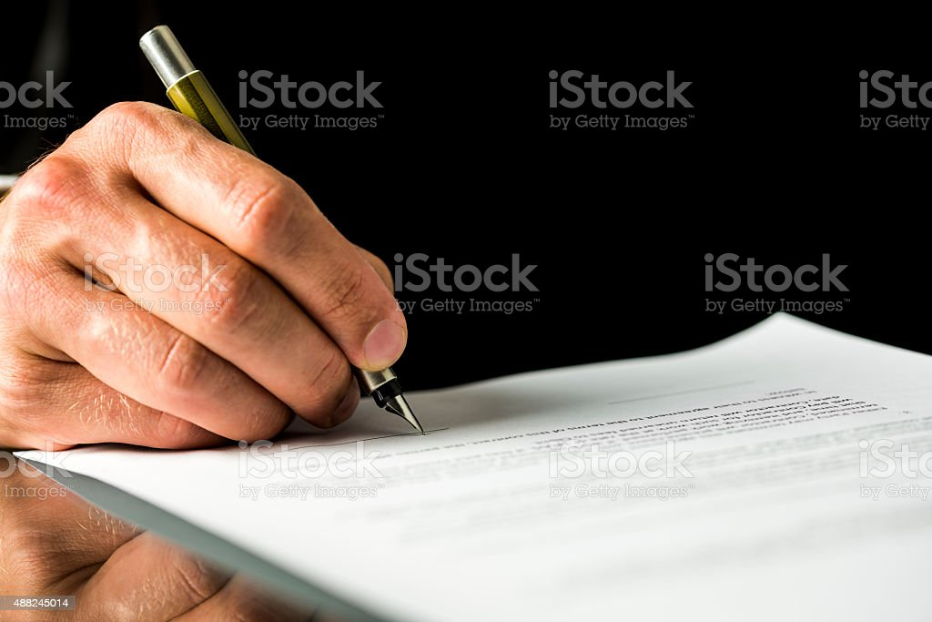 Male hand signing a contract, employment papers, legal document stock photo