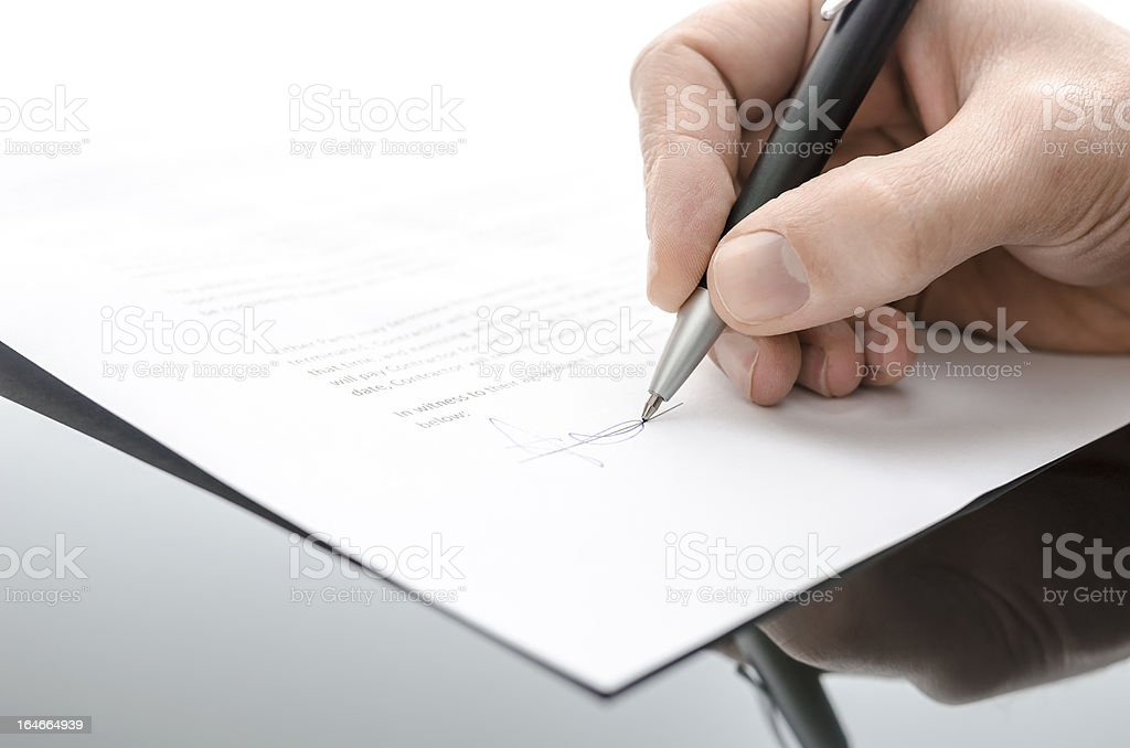 Male hand signing contract on a black table royalty-free stock photo