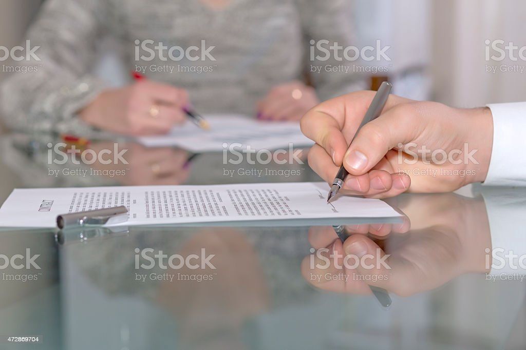 Male hand signing formal paper stock photo