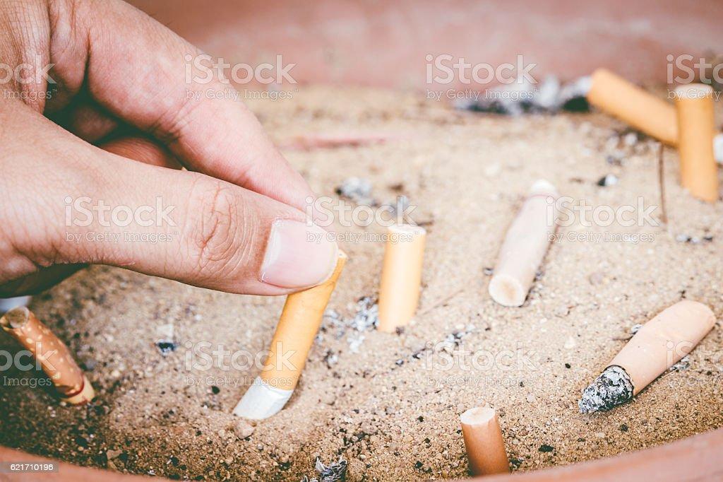 Male hand Stubbing Out Cigarette in sand ashtray bin stock photo