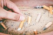 Male hand Stubbing Out Cigarette in sand ashtray bin