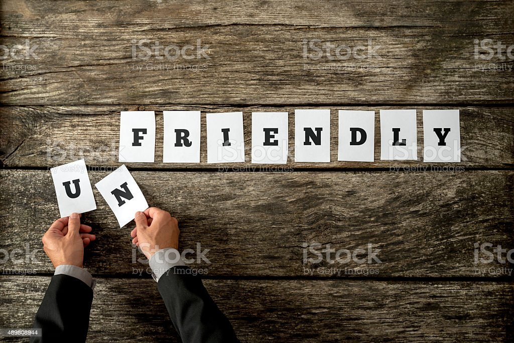 Male hand taking away letters UN from the word unfriendly stock photo