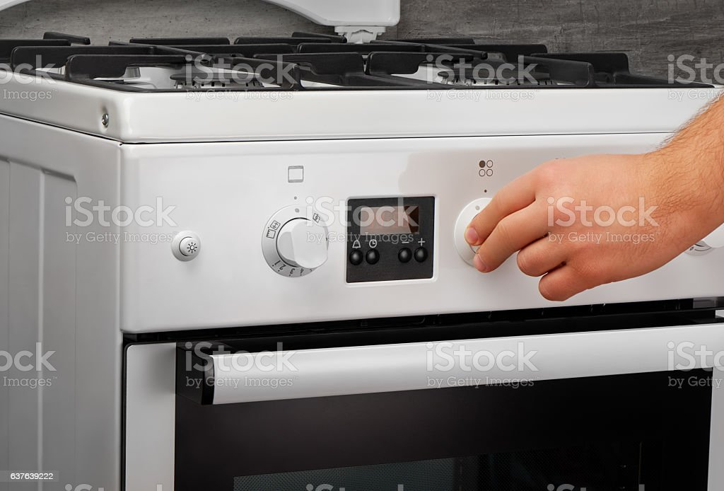 Male hand turning on white kitchen gas stove on gray stock photo