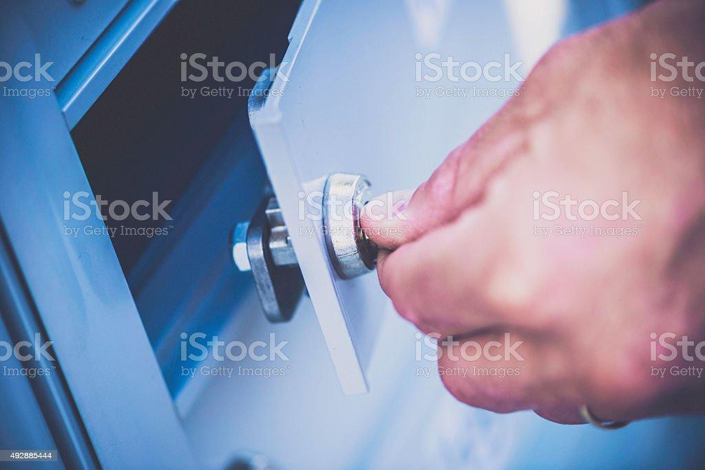Male hand unlocking door on mailbox or safety deposit box stock photo