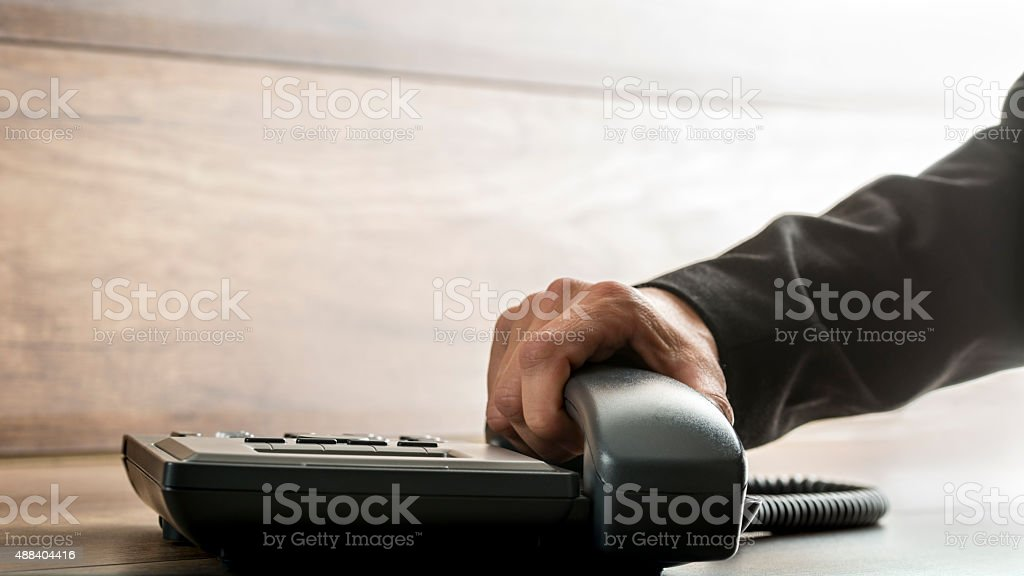 Male hand with black sleeve suit picking up  telephone  receiver stock photo