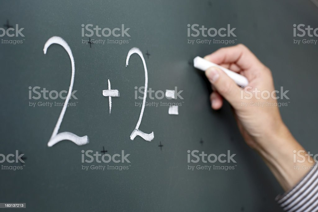 Male hand with chalk calculating on a black board stock photo
