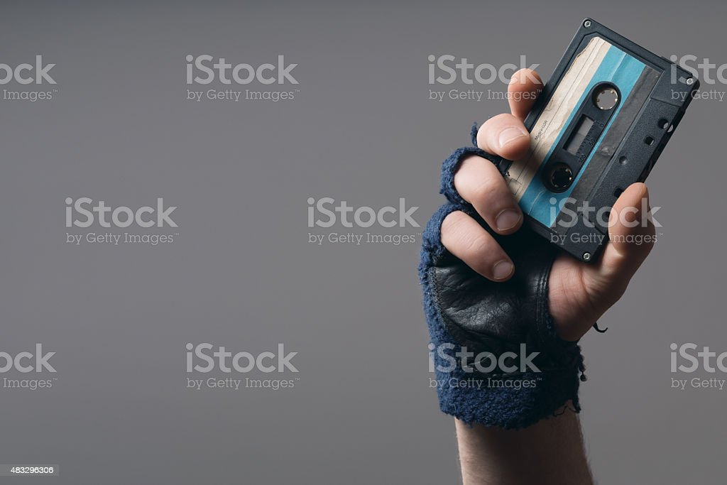 male hand with glove holding an old music tape stock photo